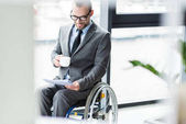 physically handicapped businessman drinking coffee
