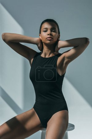 Photo for African american elegant fashion model in black bodysuit posing and looking at camera - Royalty Free Image