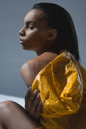 Photo for Sensual young african american woman in wet yellow raincoat posing in studio - Royalty Free Image