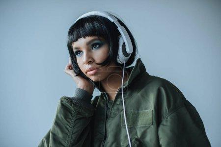 Photo pour Portrait de femme en casque regardant loin isolé sur gris - image libre de droit