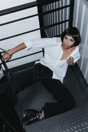 Woman in cuffs sitting on floor