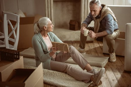 Photo for Senior wife showing old photo to her husband while taking break from packing cardboard boxes, moving out concept - Royalty Free Image