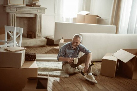 Photo for Happy senior man sitting on floor with cup of tea and taking break from packing cardboard boxes, moving out concept - Royalty Free Image