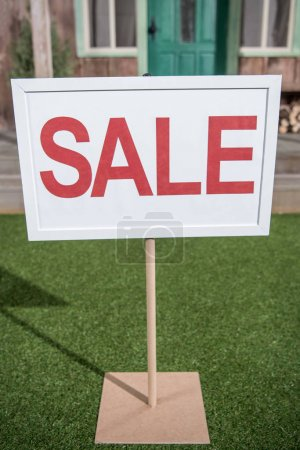 Photo for White sale banner standing on grass near new house - Royalty Free Image