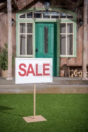 Photo pour Bannière de vente blanche debout près du porche de la maison neuve, concept de maison à vendre - image libre de droit