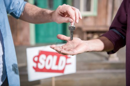 Photo for Cropped view of man buying new house and taking keys, sold sign behind - Royalty Free Image