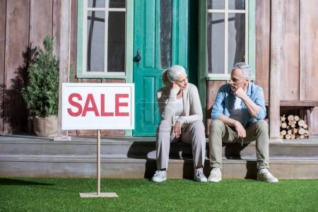 Photo for Upset senior couple sitting on porch and selling their house, house for sale concept - Royalty Free Image