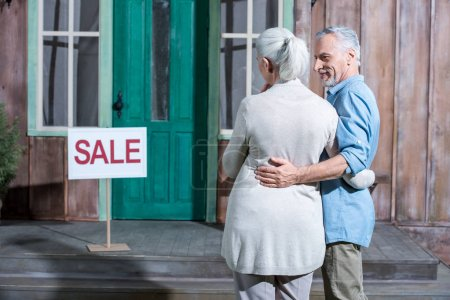 Photo for Smiling senior couple selling their house, house for sale concept - Royalty Free Image