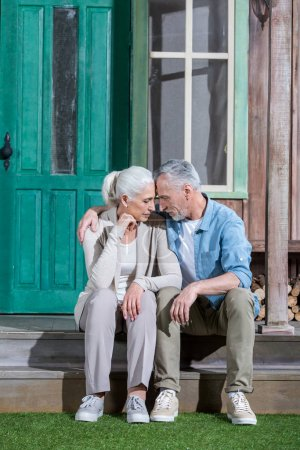 Photo for Upset senior couple hugging and sitting on porch of their house - Royalty Free Image
