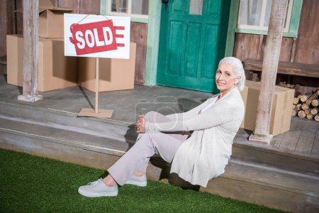 Senior woman near sold house