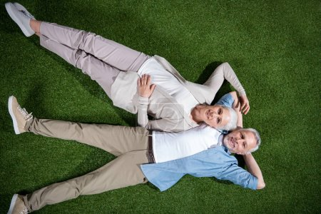 Photo for Top view of happy senior couple lying together on green grass and smiling at camera - Royalty Free Image