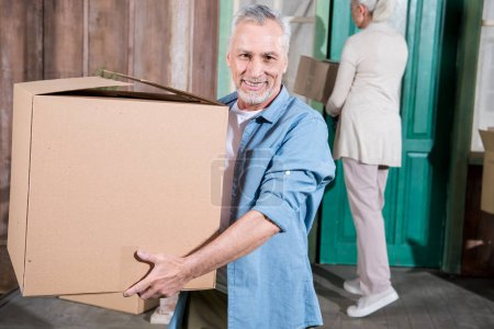 Photo for Happy senior man holding cardboard box and smiling at camera - Royalty Free Image