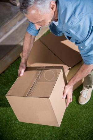 Photo for Senior man standing on green grass and holding big cardboard box - Royalty Free Image