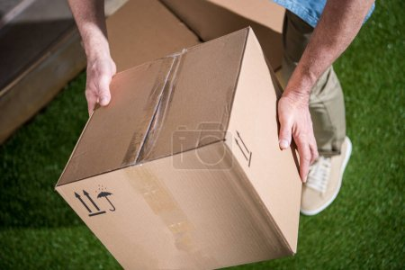 Photo for Cropped shot of man holding cardboard box above green grass - Royalty Free Image