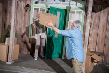 Photo for Senior man throwing cardboard box to wife standing on porch of new house - Royalty Free Image