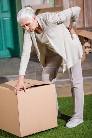 Senior woman with cardboard box