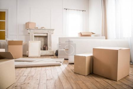 Photo for Picture frame and cardboard boxes in empty room, relocation concept - Royalty Free Image