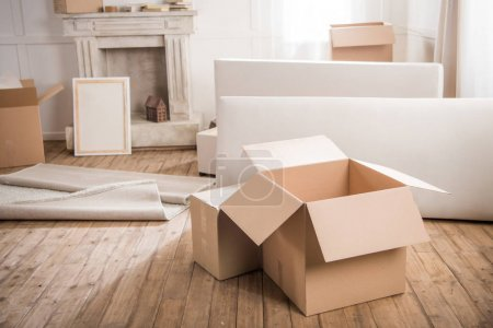 Photo for Close-up view of cardboard boxes and furniture in empty room, relocation concept - Royalty Free Image