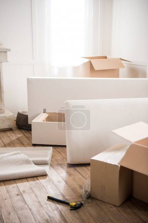 Photo for Cardboard boxes, furniture and hammer with nails in empty room, relocation concept - Royalty Free Image