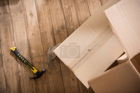 Photo for Top view of cardboard boxes with hammer and nails on wooden floor, relocation concept - Royalty Free Image