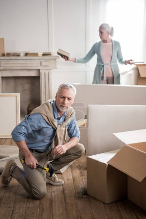 Photo for Concentrated senior man with hammer sitting on floor with wife behind - Royalty Free Image