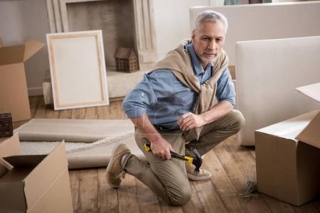 Senior man with hammer in hand
