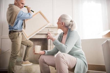 Photo pour Accrocher la photo sur le mur tandis que femme buvant du café près de l'homme - image libre de droit