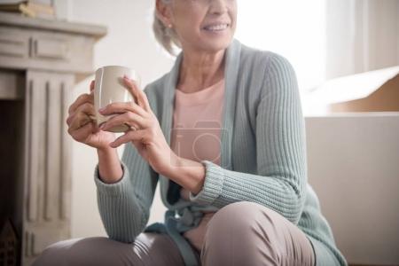 Photo pour Vue partielle de femme souriante tenant la tasse de café dans les mains - image libre de droit