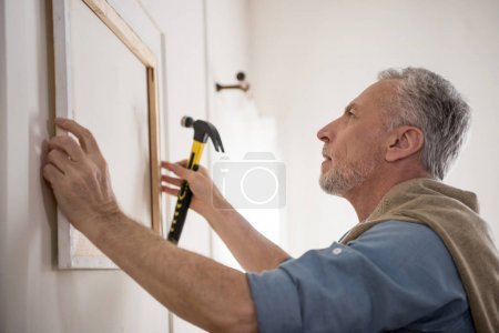 man hanging picture on wall