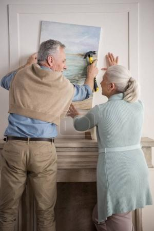 senior couple hanging picture on wall