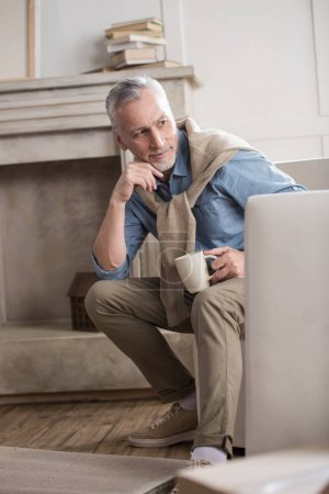 Photo for Pensive senior man with coffee cup looking away - Royalty Free Image