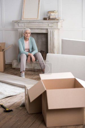 tired woman sitting on fireplace