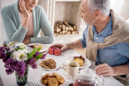 man presenting gift to wife during breakfast