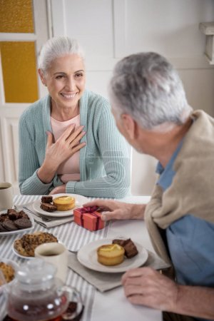 Senior man presenting gift to wife