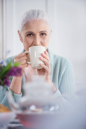 Grey haired woman drinking coffee