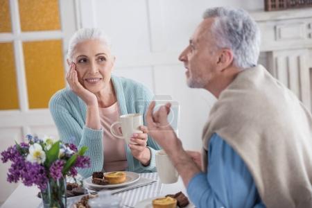 Foto de Senior pareja hablar y beber té durante el desayuno en casa - Imagen libre de derechos