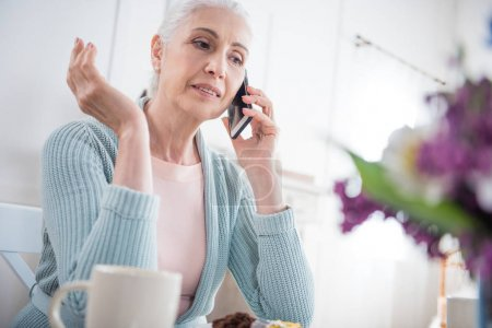 senior woman talking on smartphone at home