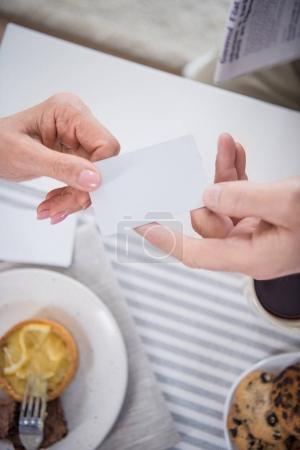 Photo pour Plan recadré de l'homme passant carte blanche à la femme pendant le petit déjeuner - image libre de droit