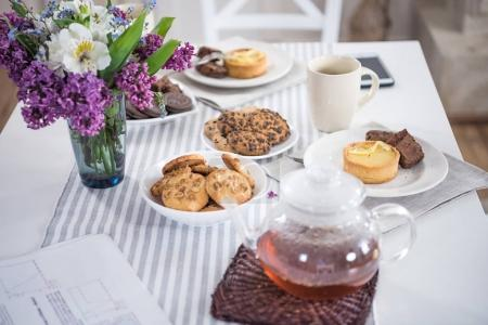 Photo for Lilac flowers with tea and various pastry with cookies on tabletop - Royalty Free Image