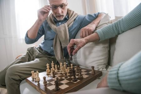 senior couple playing chess on sofa