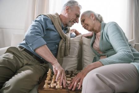 couple de personnes âgées embrassant tout en jouant aux échecs