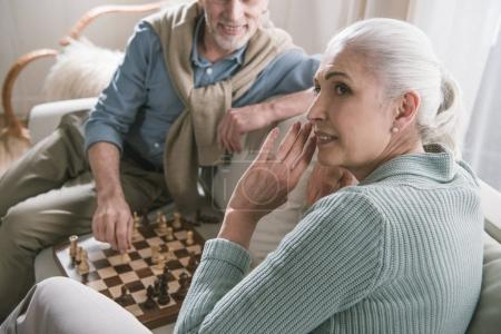 grey haired couple playing chess