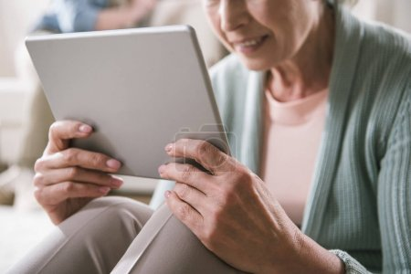 Photo for Cropped shot of senior woman using digital tablet while sitting at home - Royalty Free Image