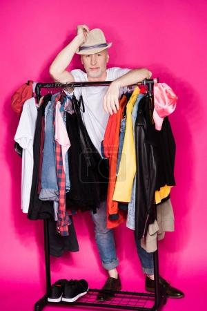 Photo for Senior man wearing hat and standing behind different clothes on hangers isolated on pink - Royalty Free Image