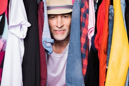 Photo for Stylish senior man wearing hat and standing with different clothes on hangers and looking at camera - Royalty Free Image
