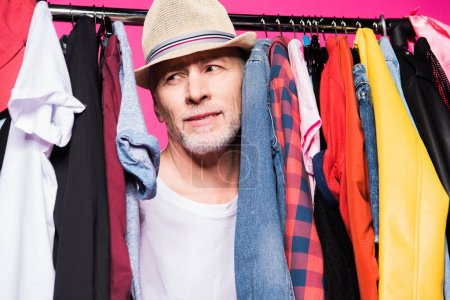 Photo for Fashionable senior man wearing hat and standing and choosing clothes isolated on pink - Royalty Free Image