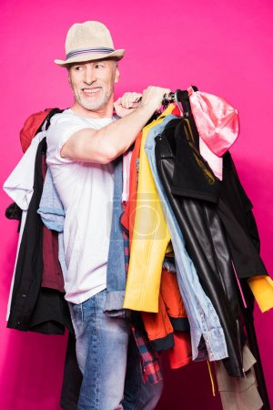 Senior man with diferent clothes on hangers