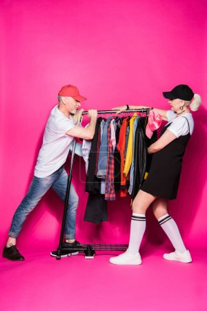 Photo for Stylish senior couple pulling wardrobe with different clothes on hangers isolated on pink, relationship difficulties concept - Royalty Free Image