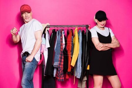 Photo pour Heureux couple sénior élégant debout avec des vêtements différents sur cintres isolés sur rose - image libre de droit