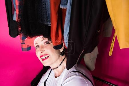 Photo for Happy senior woman sitting under clothes on hangers and looking on them isolated on pink - Royalty Free Image